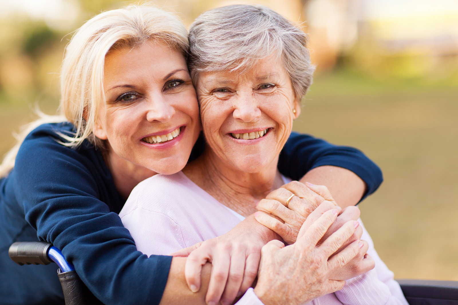 cheerful middle aged woman embracing disabled senior mother outd